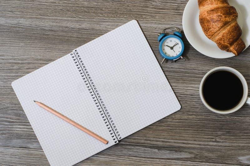 Um fim acima de um desktop com bloco de notas vazio, despertador, copo do coffe e filhós nela Fundo de madeira, vista superior fotos de stock