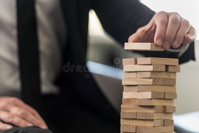Um fim acima de um homem de negócio que constrói com cuidado uma torre foto de stock