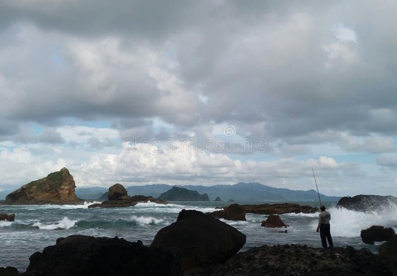 Um fisher no fundo da onda foto de stock