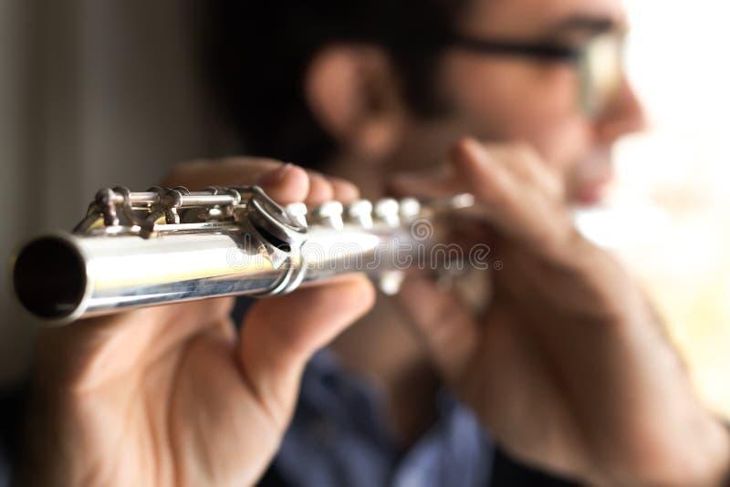 Um flautista masculino que joga, dentro foto de stock