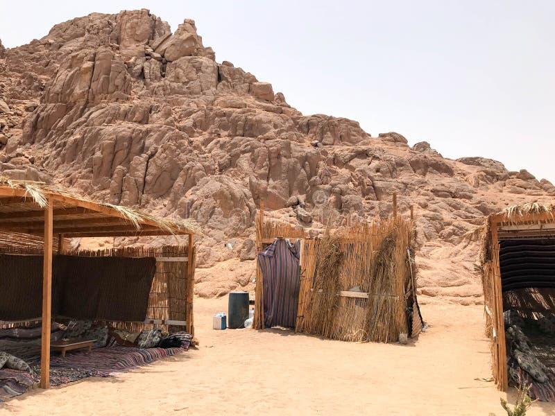 Um flimsy, moradia pobre decrépita, frágil, frágil dilapidada, uma construção beduína feita da palha, galhos em um deserto quente fotos de stock
