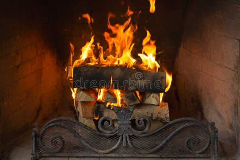 Um fogo rujir dentro de uma grande pedra arqueou a chaminé fotografia de stock royalty free