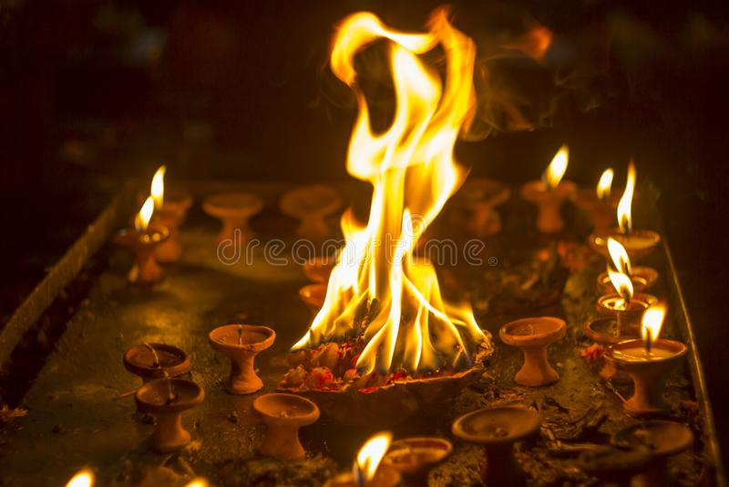Um fogo sacrificial em uma bacia com as flores nas velas escuras e pequenas Velas ardentes Incêndio na noite imagem de stock