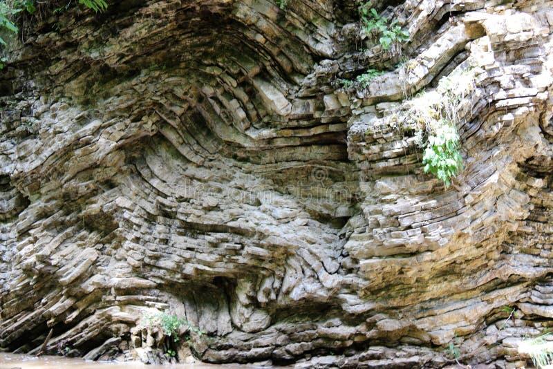 Um formulário estranho do magma endurecido para milhões de anos de magma na costa de um córrego da montanha imagens de stock royalty free