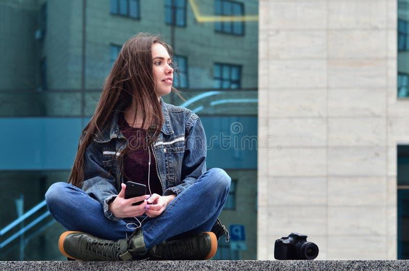 Um fotógrafo da menina usa um smartphone e senta-se em um granito para fotografia de stock