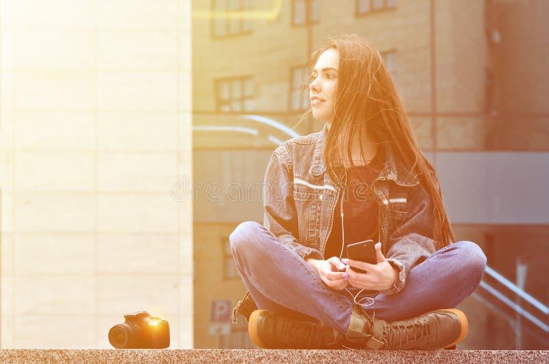 Um fotógrafo da menina usa um smartphone e senta-se em um granito para imagem de stock royalty free
