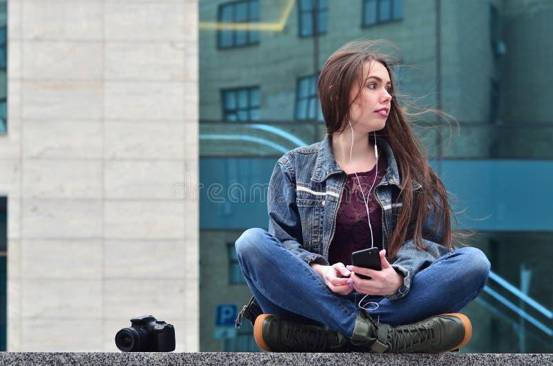 Um fotógrafo da menina usa um smartphone e senta-se em um granito para foto de stock