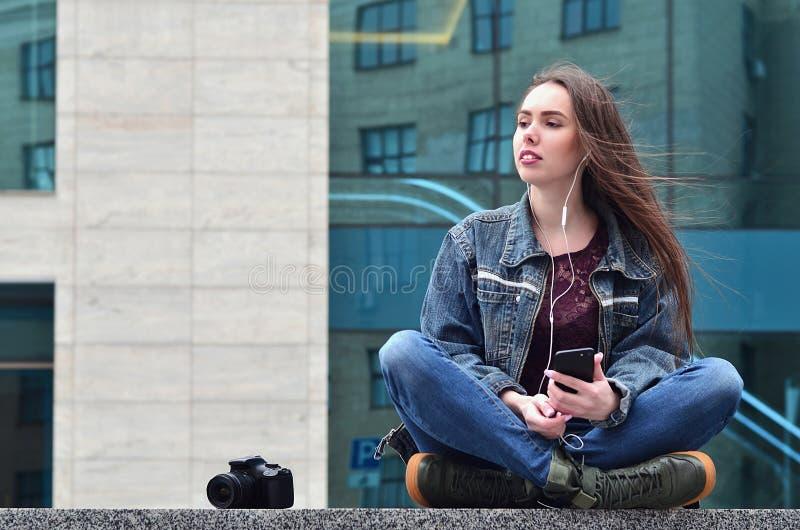 Um fotógrafo da menina usa um smartphone e senta-se em um granito para fotos de stock royalty free