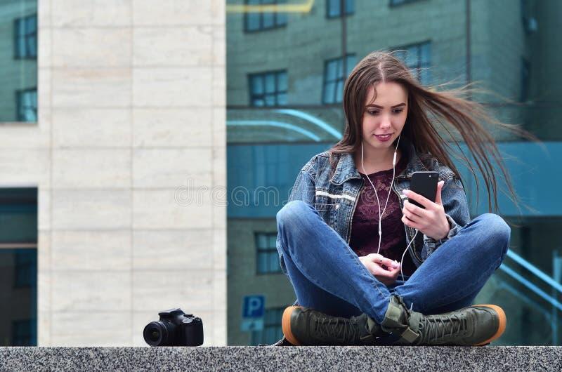 Um fotógrafo da menina usa um smartphone e senta-se em um granito para imagens de stock