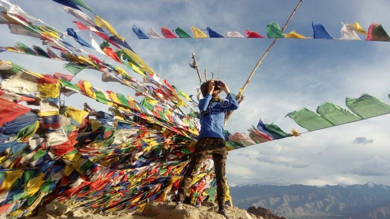 Um fotógrafo entre as bandeiras tibetanas na montanha fotos de stock