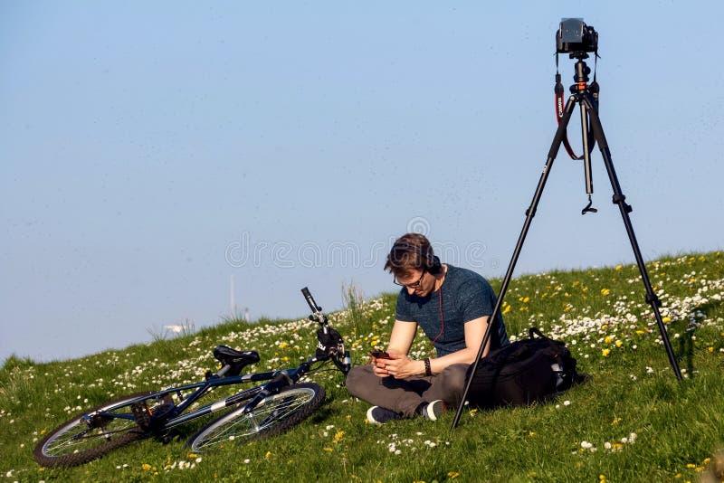 Um fotógrafo novo que espera o por do sol fotografia de stock