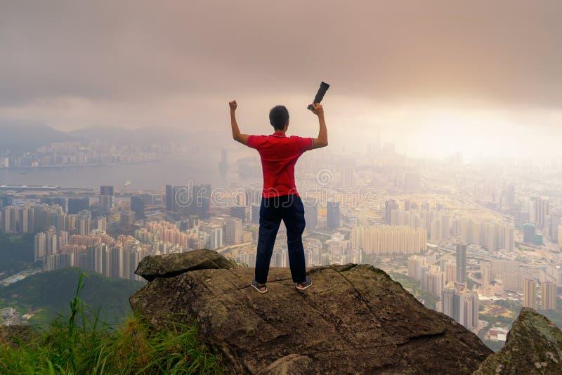 Um fotógrafo que caminha e que olha a cidade na rocha, monte da montanha na baixa de Hong Kong no conceito da aventura durante a  imagens de stock