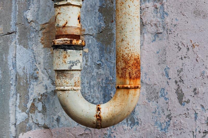 Um fragmento da tubulação de água oxidada velha no fundo gasto da parede fotografia de stock royalty free
