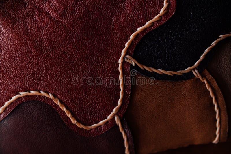 Um fragmento de um saco de couro e de uma bolsa feitos de partes multi-coloridas Costura do couro branco foto de stock