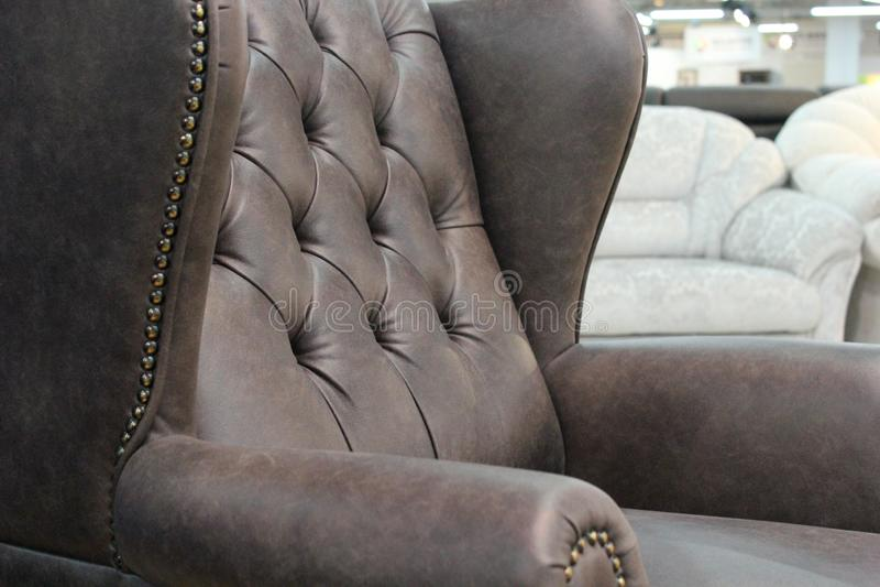 Um fragmento de uma cadeira de couro clássica Close-up da textura de couro elegante com botões Fragmento de uma cadeira clássica  imagens de stock royalty free