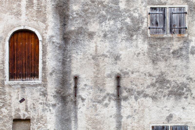 Um fragmento de uma casa abandonada velha com uma porta fechado e uma janela cega shuttered fotos de stock royalty free