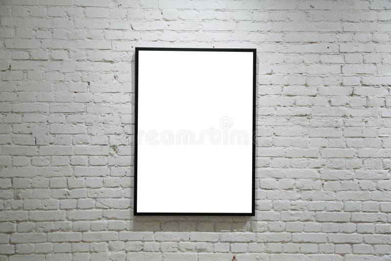 Um frame preto na parede de tijolo branca fotografia de stock