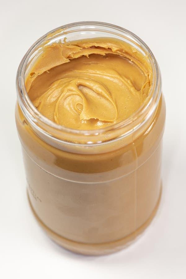 Um frasco da manteiga de amendoim orgânica que senta-se na mesa de cozinha que espera para ser comido imagem de stock