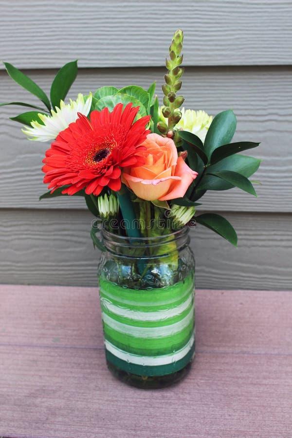 Um frasco de pedreiro com flores da mola fotografia de stock royalty free