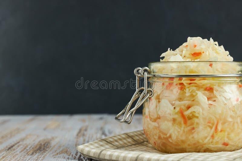 Um frasco do chucrute e das cenouras em seu próprio suco com especiarias em uma luz, tabela de madeira branca, fundo preto, vista imagem de stock royalty free