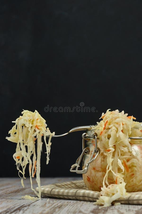 Um frasco do chucrute e das cenouras em seu próprio suco com especiarias em uma luz, tabela de madeira branca, fundo preto, vista foto de stock royalty free