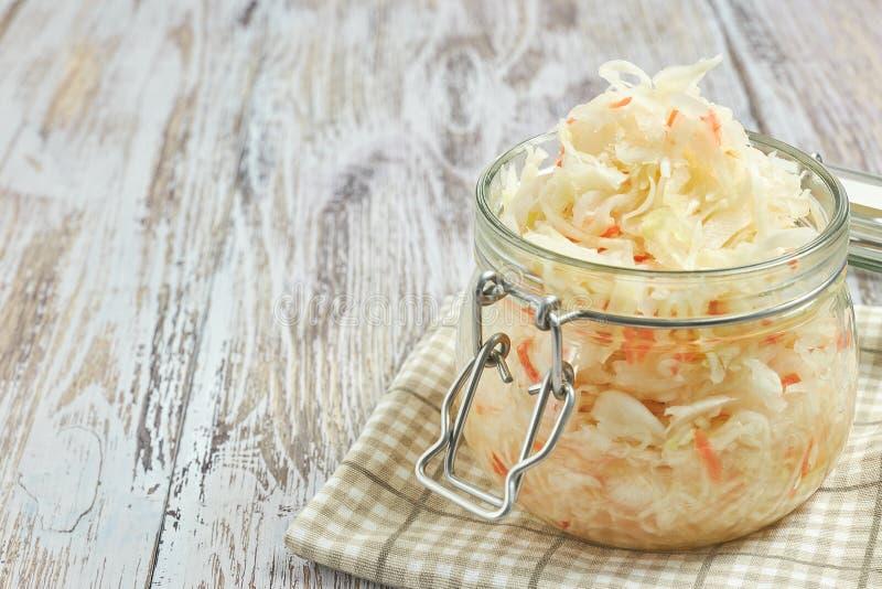 Um frasco do chucrute e das cenouras em seu próprio suco com especiarias em uma luz, tabela de madeira branca, um tipo vertical d foto de stock royalty free