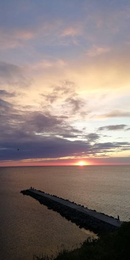 Um fundo brilhante simbólico bonito Seascape de alarme do outono Povos da silhueta em um cais de pedra fotos de stock royalty free