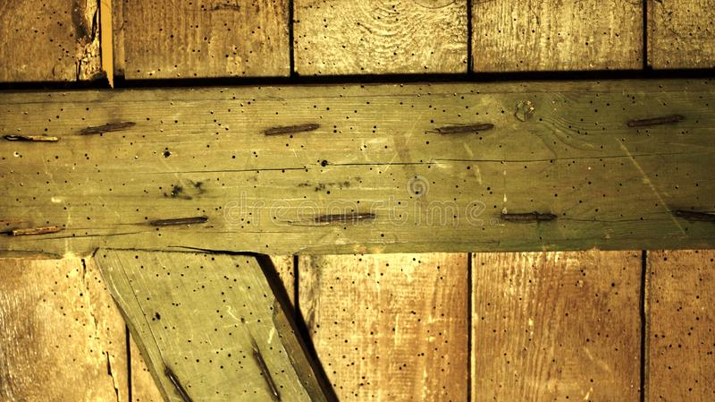 Um fundo de madeira contínuo feito de vertical velho e uma placas horizontais e uma dobrada, conectado por pregos foto de stock
