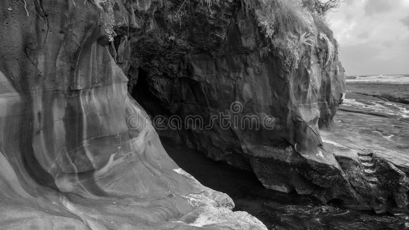 Um furo na rocha em um penhasco perto de uma praia imagens de stock royalty free