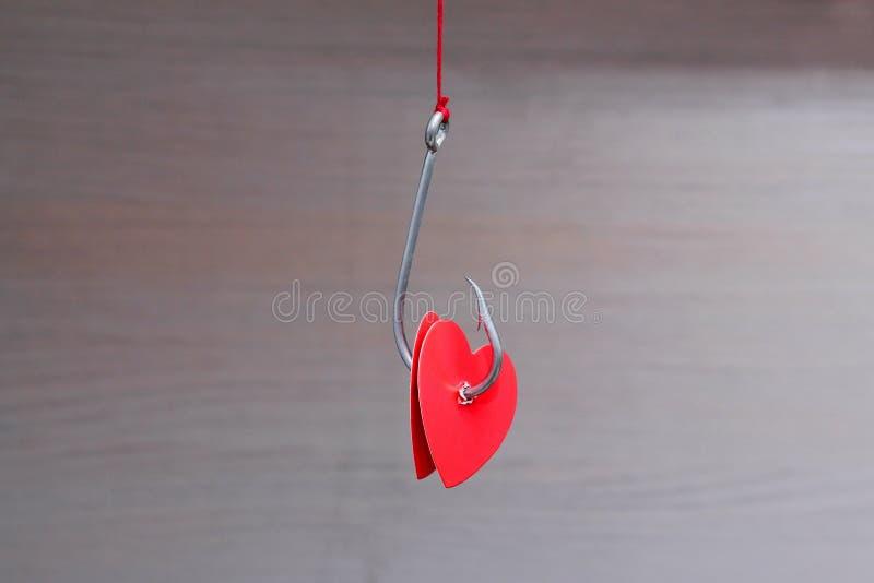 Um gancho de pesca do metal que pendura em corações perfurados corda de um reboque do cartão vermelho Conceito do amor Dia do `s  fotos de stock
