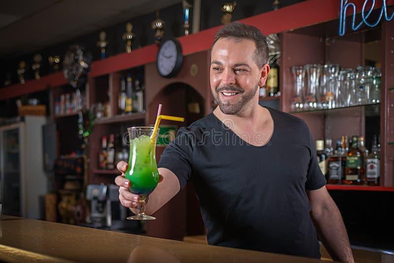 Um garçom de sorriso serve um cocktail em um contador foto de stock royalty free