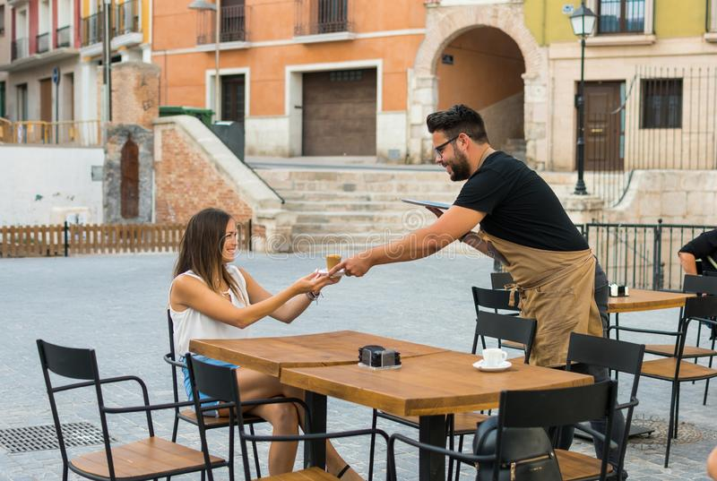Um garçom está servindo um café a uma jovem mulher em um terraço do bar imagens de stock