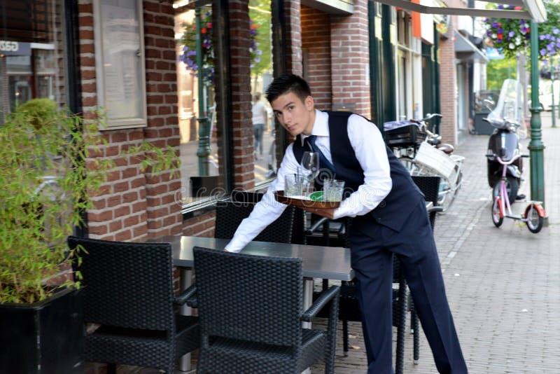 Um garçom novo está no trabalho em Hoorn, Holanda foto de stock