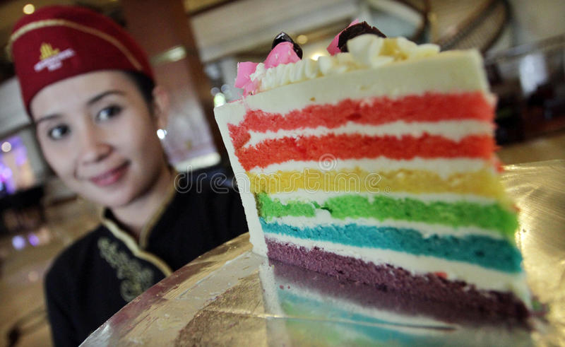 Um garçom traz o bolo do arco-íris fotos de stock royalty free