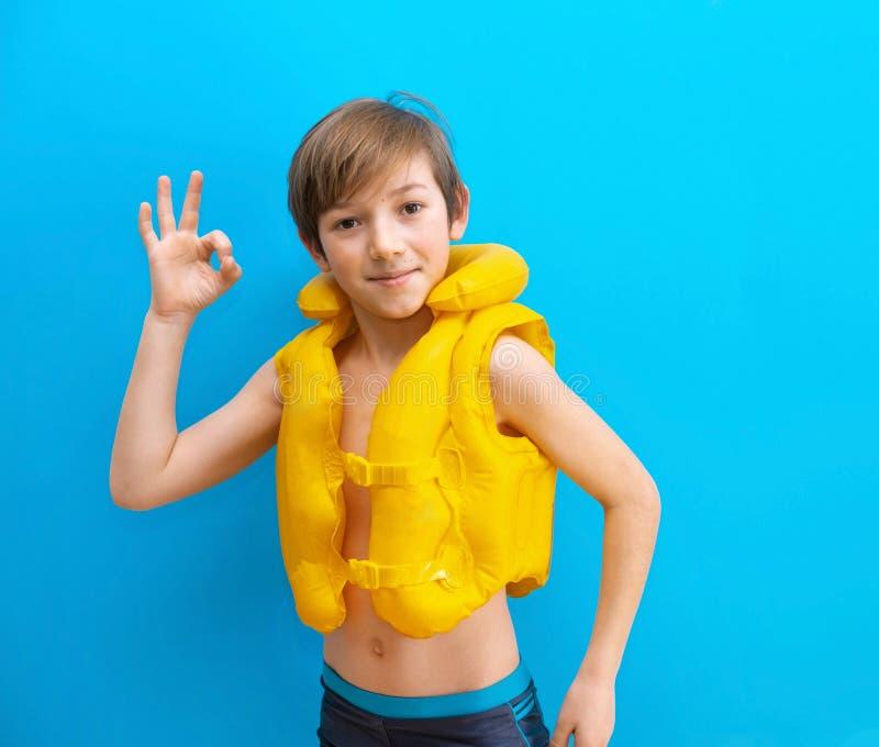 Um garoto de 9 anos em um colete inflável mostra um bom sinal Bom descanso no mar e no parque aquático Viagens marítimas fotografia de stock royalty free