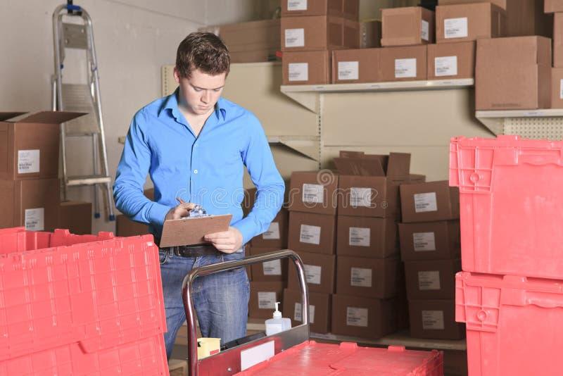 Um gerente bonito do armazém que verifica o inventário fotos de stock royalty free