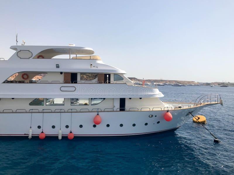 Um grande barco de três andares branco, um navio, um forro do cruzeiro com boias de vida, vigias em um recurso do sul morno tropi imagens de stock royalty free