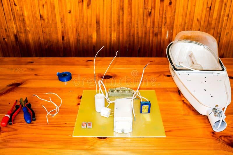 Um grande branco desmontou a lâmpada de rua com um circuito bonde com fios e peças sobresselentes, equipamento da instalação, ali imagem de stock royalty free