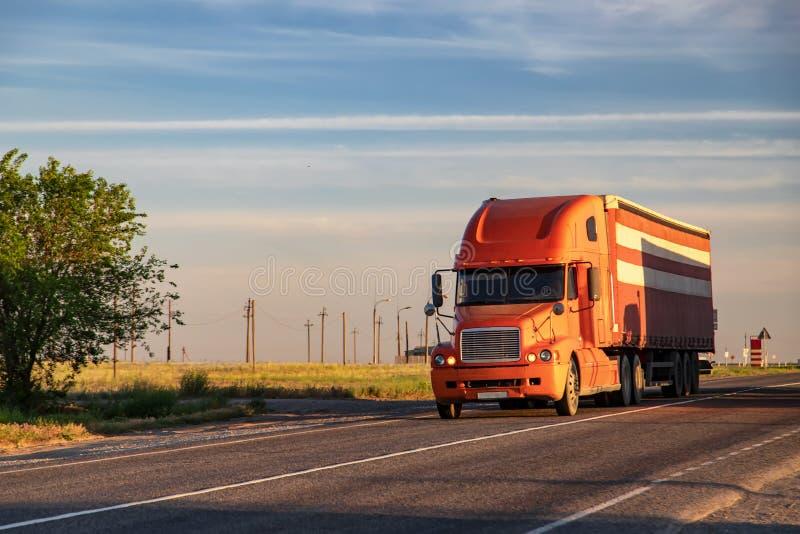 Um grande caminhão vermelho transporta bens em uma estrada interurbana fotografia de stock
