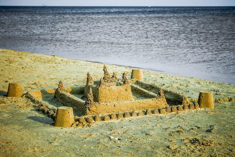Um grande castelo da areia construído pelas mãos das crianças imagem de stock royalty free