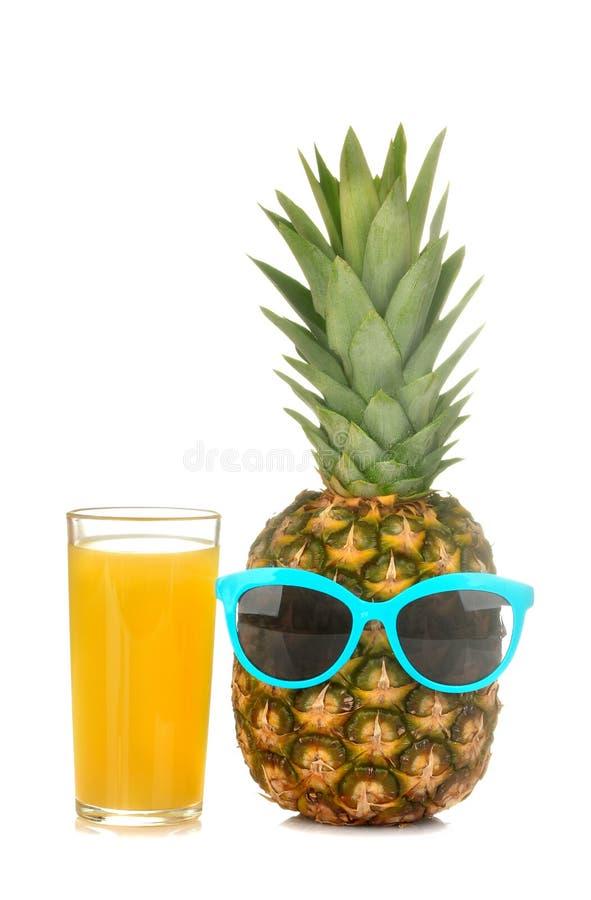 Um grande fruto maduro fresco do abacaxi nos óculos de sol com suco de abacaxi em um fundo isolado branco Fruto do ver?o imagem de stock