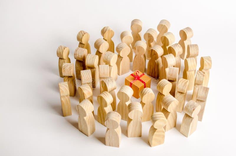 Um grande grupo de pessoas cerca a caixa de presente O conceito de escolher um bom presente, número limitado, vendido toda para f imagem de stock royalty free