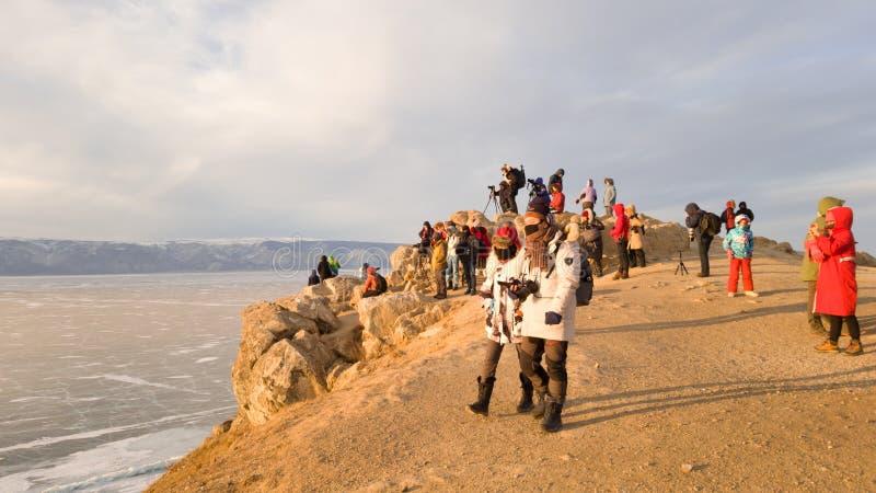 Um grande grupo de turistas no cabo Burkhan na rocha de Shamanka na ilha de Olkhon em Rússia em antecipação ao por do sol imagens de stock