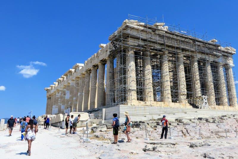 Um grande grupo de visitantes que admiram o Partenon sobre a acrópole em um dia ensolarado quente durante um dia de verão em Aten fotografia de stock royalty free