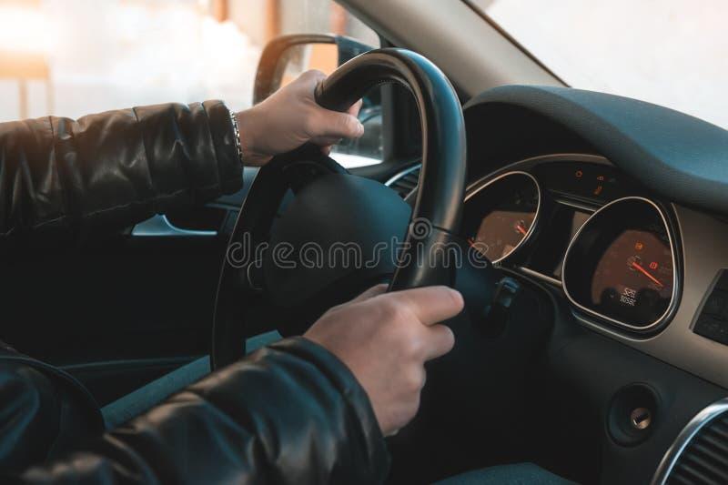 Um grande homem em um casaco de cabedal e em calças de brim senta-se atrás da roda de um carro fotos de stock