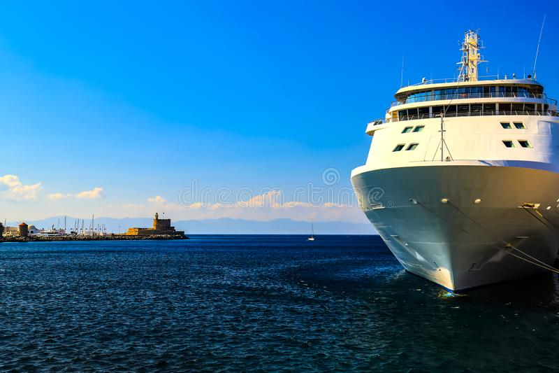 Um grande navio de cruzeiros branco está no cais no porto do turista, o Rodes, Grécia fotografia de stock