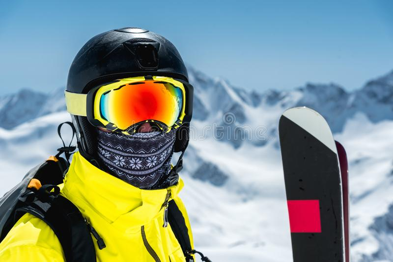 Um grande retrato de um esquiador em um capacete protetor e em vidros - uma máscara e de um lenço ao lado dos esquis contra a nev fotografia de stock royalty free
