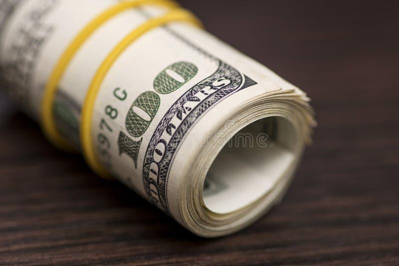 Um grande rolo de cem notas de dólar feitas malha por um elástico amarelo isolado no fundo de madeira Rolo de cem d?lares fotos de stock royalty free