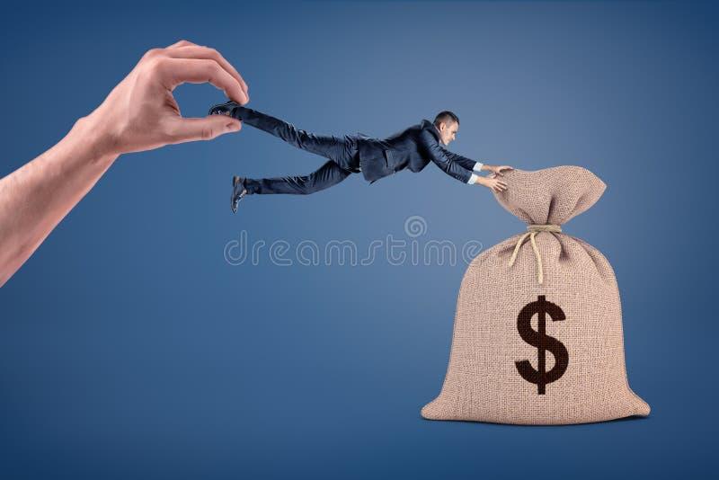 Um grande saco do dinheiro atrai um homem de negócios pequeno que seja arrastado afastado por uma mão gigante fotografia de stock royalty free