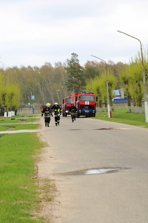 Um grande veículo de socorro do fogo vermelho, um caminhão para extinguir um fogo e sapadores-bombeiros do homem em um produto qu fotos de stock royalty free